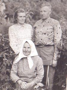Stovi Cecilija ir Pranas Kliukai, sėdi bobutė Elenora