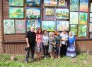 """Respublikinio tapybos plenero dalyviai prie savo darbų, eksponuojamų ant bendruomenės namų """"Strėva"""" sienos"""