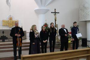 Bažnyčioje koncertavę Elektrėnų meno mokyklos mokytojai šypsosi prie vargonų stovinčiai Rūtai Striškaitei