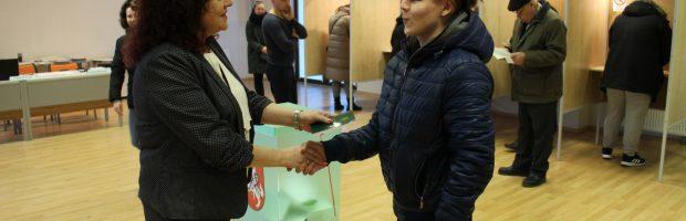 Sodų rinkimų apylinkės pirmininkė Violeta Smilgevičė  Lietuvos Konstituciją įteikia Ričardui Vaicekauskui