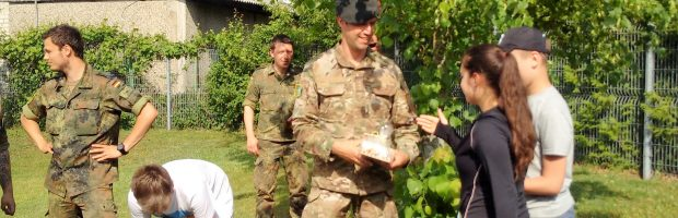 Mokinių lauktuvės kariams - keksiukai įteikiami kapitonui Merien