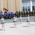"""Šoka Vievio pradinės mokyklos grupė """"Boružėlės"""", groja Elektrėnų meno mokyklos pučiamųjų orkestras, stovi šaulių kuopa"""