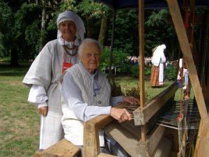 2018 m. Dainų šventėje staklėse sėdi Lietuvos audėjų audėja Monika Kriukelienė, gim. 1920 m.