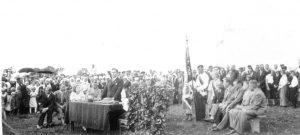 """III Lietuvos evangelikų jaunimo draugijos """"Radvila"""" jaunimo ir giesmių šventės dalyviai iškilmingo posėdžio metu. Šventė įvyko 1937 m. liepos 11 d. Papilyje. Joje dalyvavo 500 radvilėnų, 44 Klaipėdos jaunieji sandoriečiai su savo choru ir orkestru ir daugybė svečių iš įvairių evangelikų parapijų. Dalyviai, grojant orkestrui, nešdami vėliavą žygiavo per Papilio miestelį į iškilmingą posėdį. Prie stalo iš kairės garbės svečiai: kun. Vytautas Kurnatauskas (pasisukęs šonu), Biržų žemės ūkio draugijos pirmininkas Jonas Mekas, pranešimą apie nuveiktus darbus skaito """"Radvilos"""" draugijos steigėjas ir centro valdybos pirmininkas kun. Aleksandras Balčiauskas. Nuotrauka iš Biržų muziejaus archyvo"""
